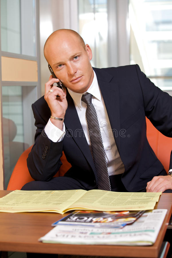 Businessman conversing on mobile phone, portrait stock images