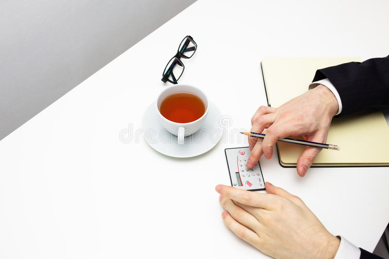 Businessman counting on calculator with cup of tea on white background. royalty free stock photo