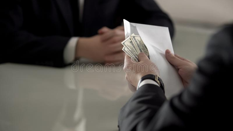 Businessman counting money in envelope, bribe to official, corruption concept. Stock photo royalty free stock image