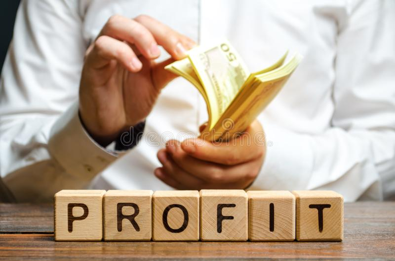 Businessman counting money in hands and inscription Profit. Fixation of income and return on investment with interest earnings. stock image