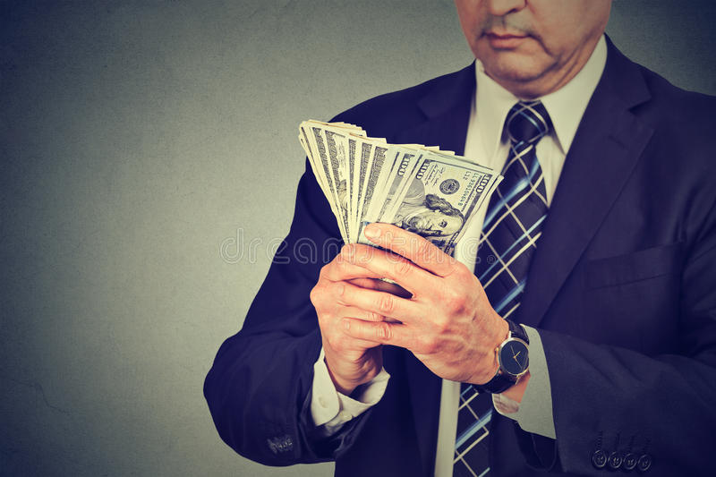 Businessman counting money. Middle aged businessman counting money stock photo