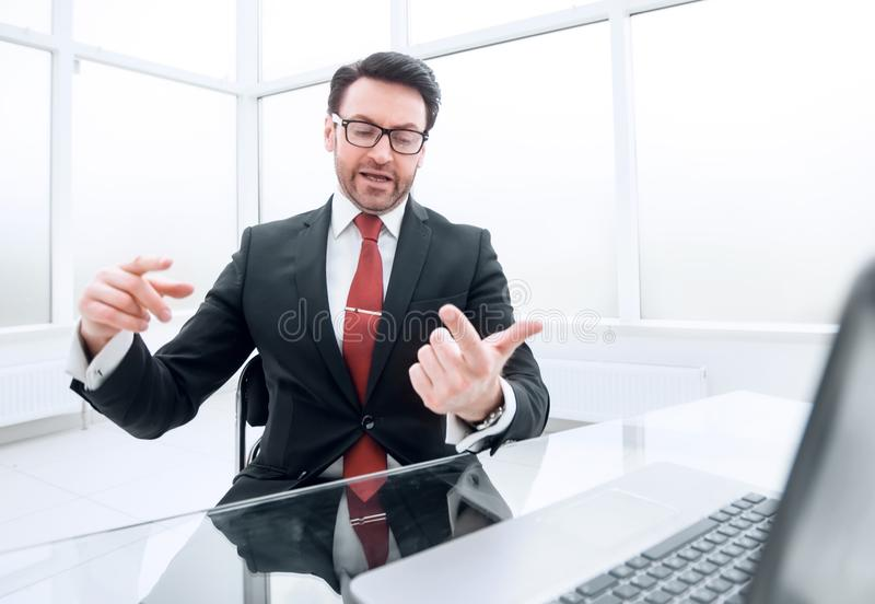 Businessman counts on his fingers, sitting at his Desk. stock photo