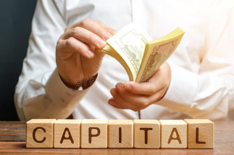 Businessman counts money on the background of the caption Capital. Capitalism, capital increase and influence. Financial stock photo