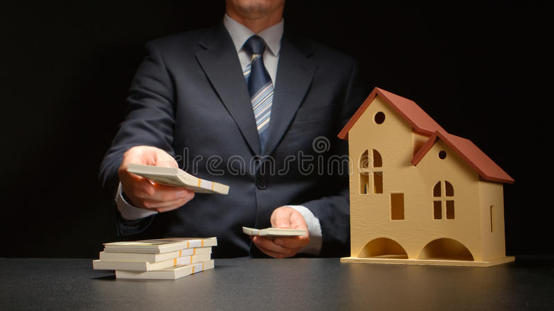 Businessman counts a money stack near a house model on a table stock photography