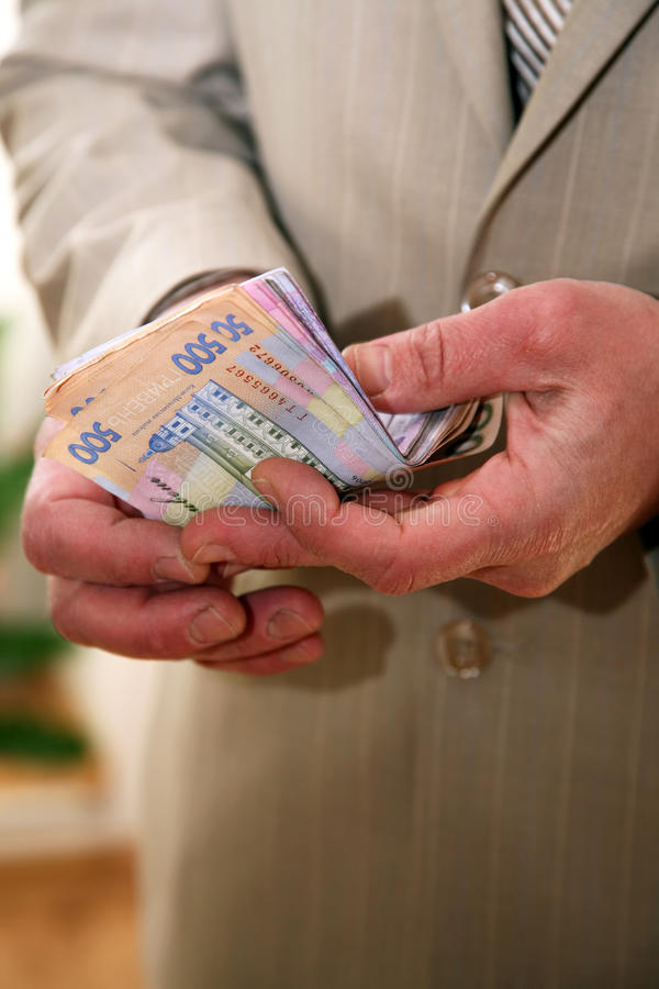 Businessman counts money in Ukrainian currency stock photography