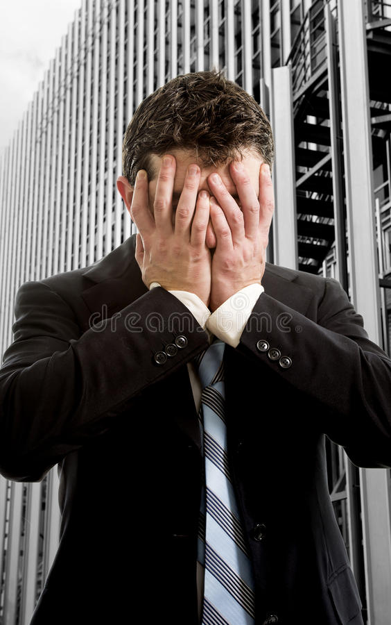 Businessman covering face desperate in front of office building business district stock photo