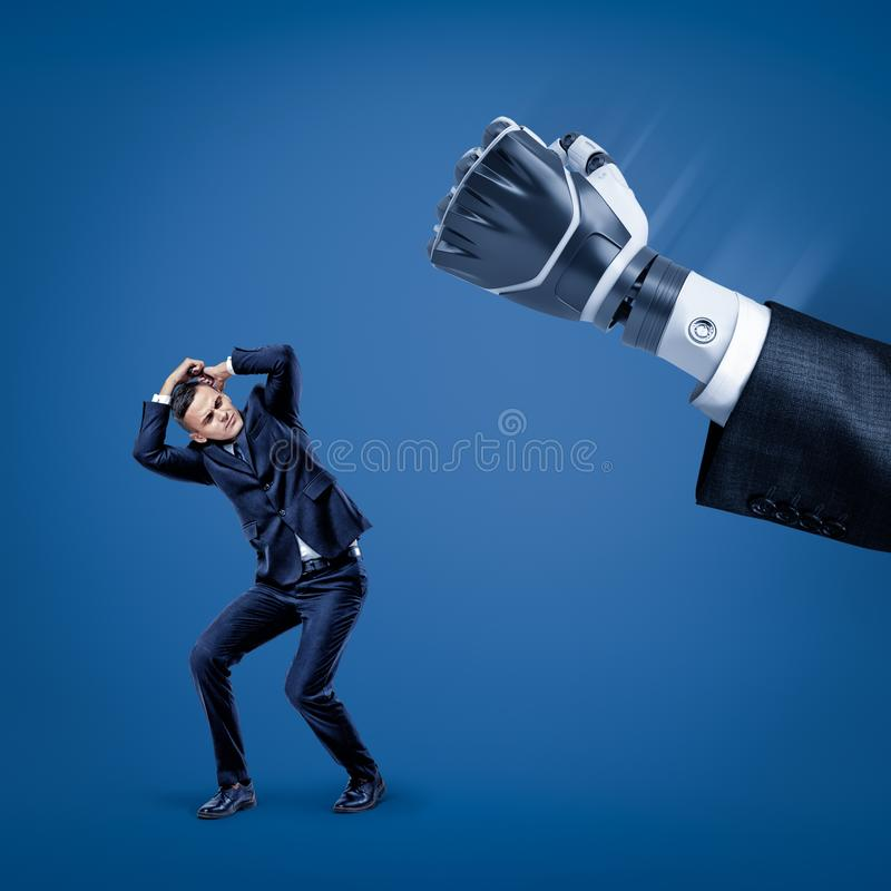 Businessman covering his head with hands to protect himself from big robot hand in suit. Problems with business. AI replaces humans. Big failure royalty free stock images