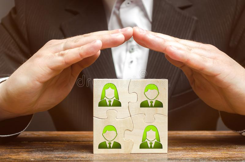 Businessman covers with hands the business team of employees. Patronage support, encouragement, privilege and financial aid. stock photography