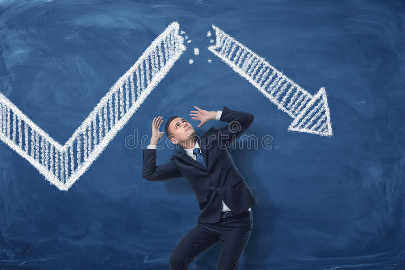 Businessman cowering on blue blackboard background with chalk drawing of white statistic arrow broken in half. Business management. Profit and loss. Business royalty free stock photography