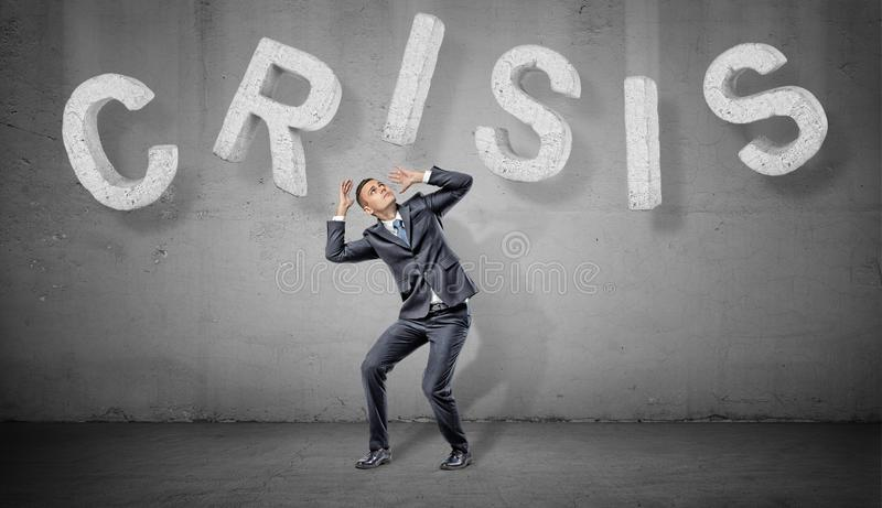 A businessman cowers under large concrete letters making up a word Crisis above him. Problems and solutions. Difficulties. Business troubles royalty free stock photography