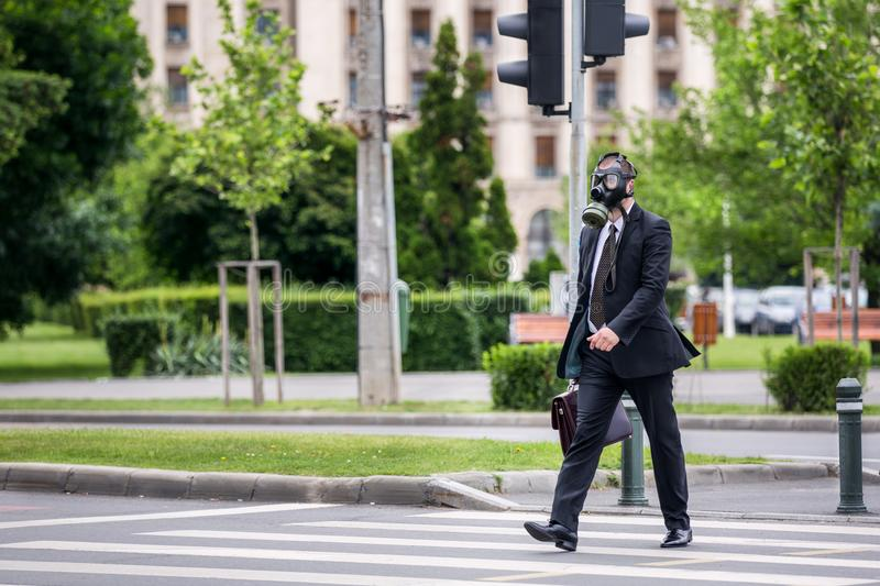 Businessman cross the street outdoor wearing a gas mask on the face. royalty free stock image