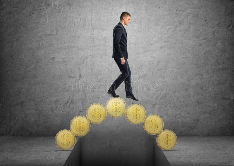 Businessman crossing a bridge made of golden coins stock photography