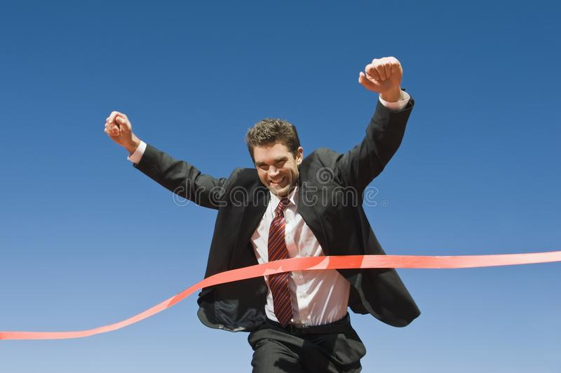 Businessman Crossing The Finish Line royalty free stock photography