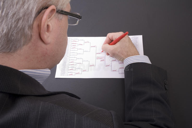 March Madness Businessman Crossing Out Teams on Bracket. A businessman crossing out teams on his busted March Madness bracket royalty free stock photos