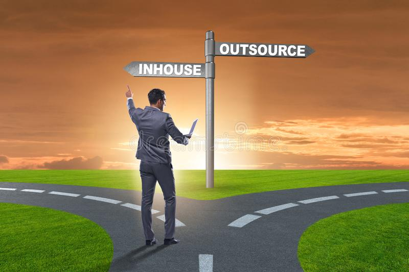 Businessman at crossroads deciding between outsourcing and inhou stock images