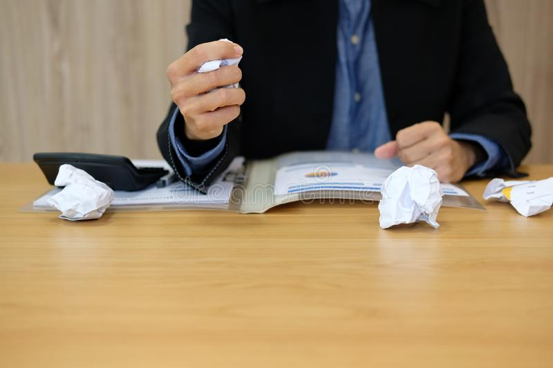 Businessman crumples crushs paper feeling furious, frustrated & stressed from hard work. At office stock photos