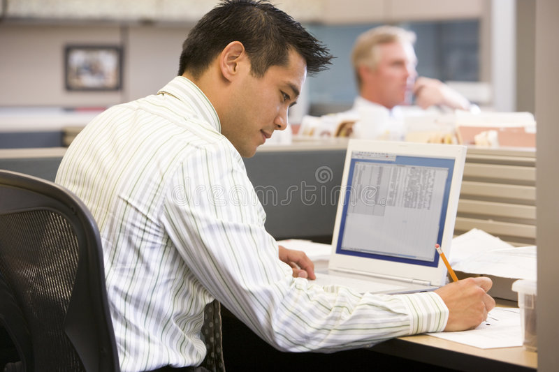 Businessman in cubicle with laptop writing royalty free stock image