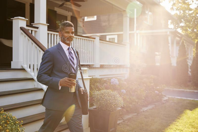 Businessman With Cup Of Coffee Leaving Suburban House For Work stock photos