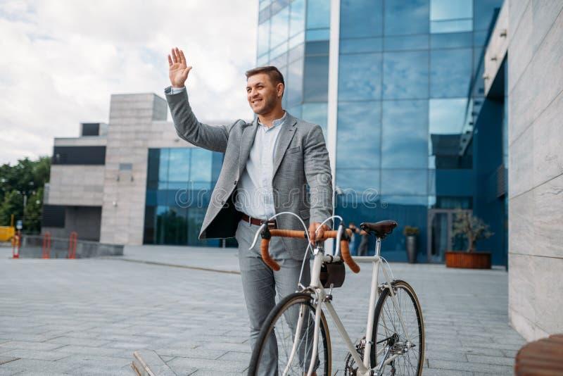 Businessman cyclist, glass building on background stock photos
