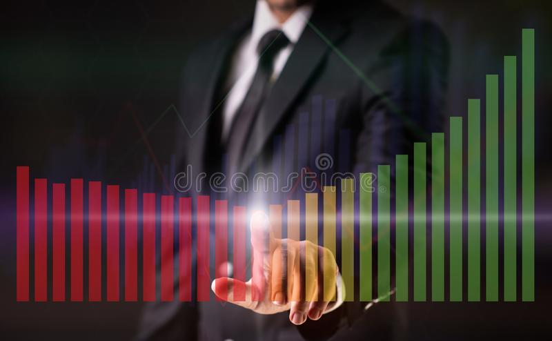 Businessman on Dark Background Touching on Virtual Screen with Financial Figures and Graphics royalty free stock photo
