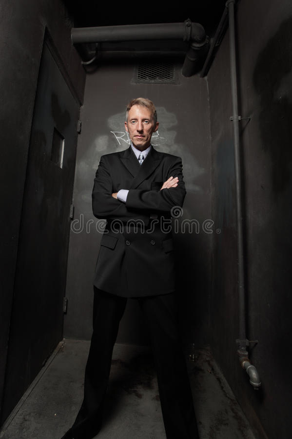 Businessman in a dark grungy alley royalty free stock images