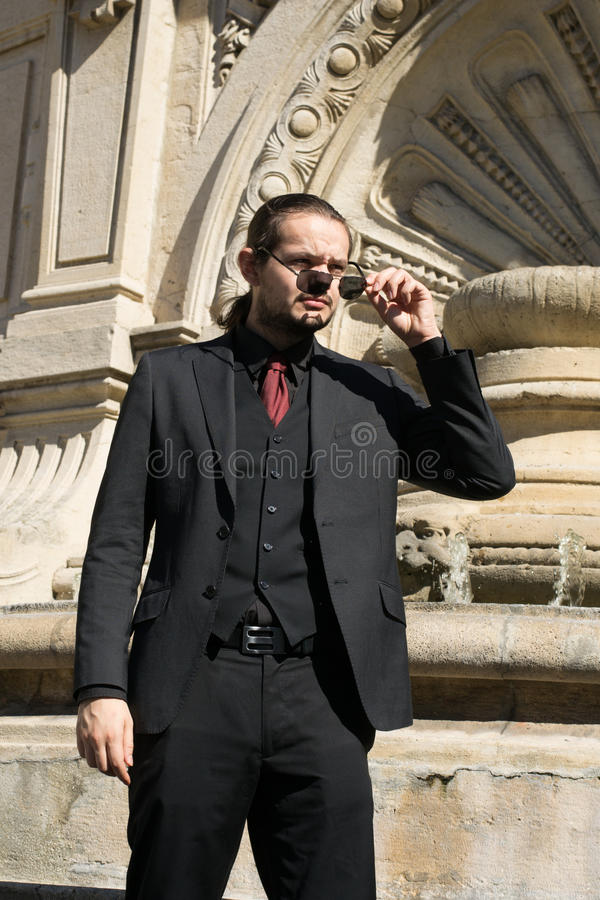 Businessman with dark suit and and glasses looking at the sun royalty free stock photography