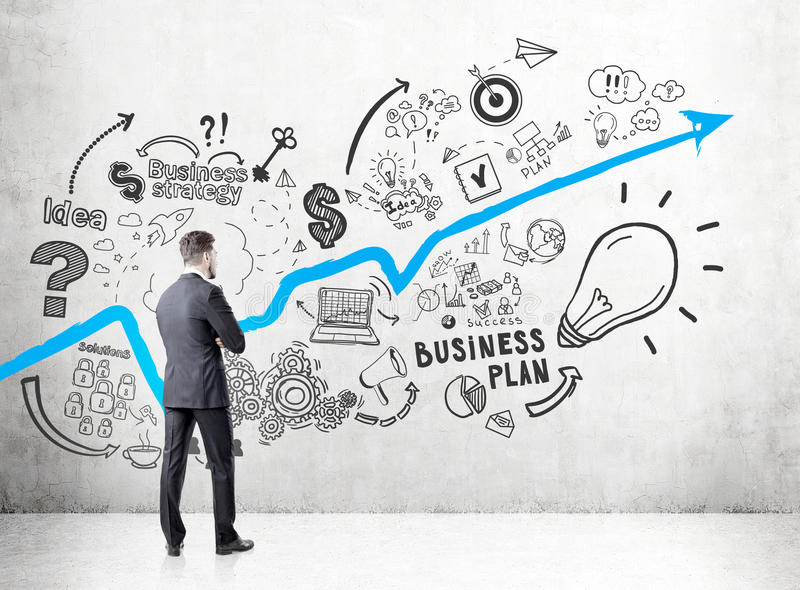 Businessman in a dark suit looking at a concrete wall with a growing blue graph and business plan icons depicted on it. royalty free stock image