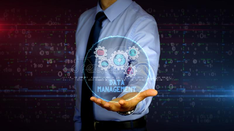 Businessman with data management hologram. Man with dynamic data management symbols hologram on hand. Businessman and futuristic concept of Files storage, cyber royalty free stock photo