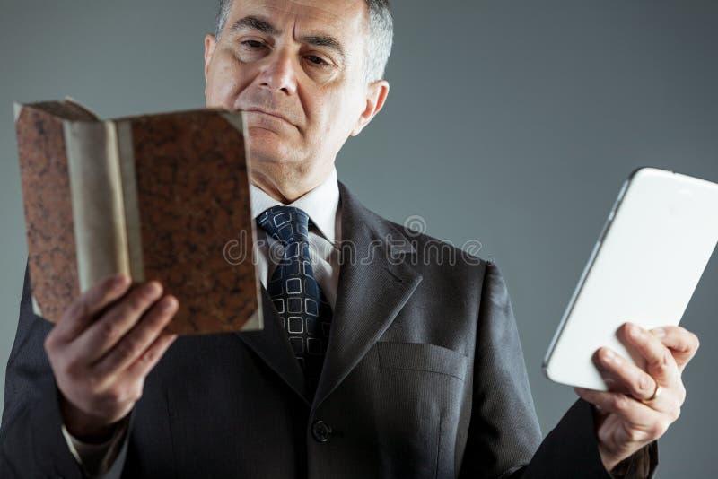 Businessman deciding between a book or e-book royalty free stock photo