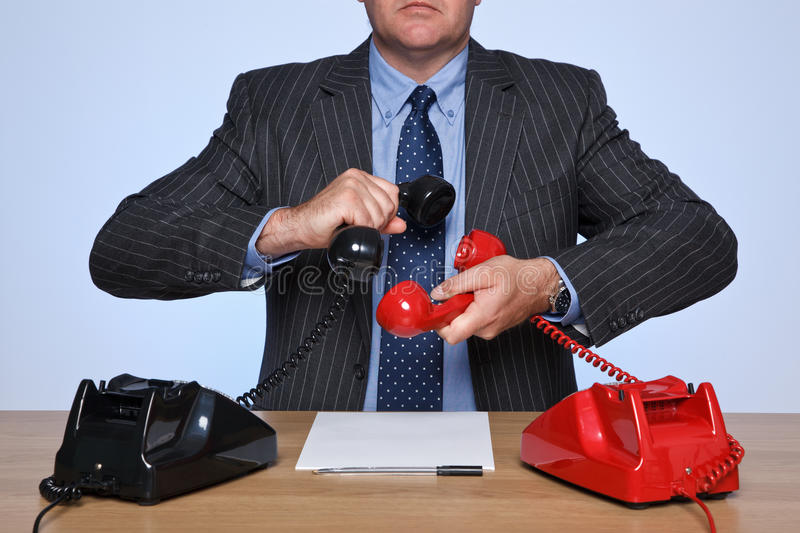 Businessman at desk on a conference call. Photo of a businessman sat at a desk holding two traditional telephones together, one red and one black. Conference stock photo