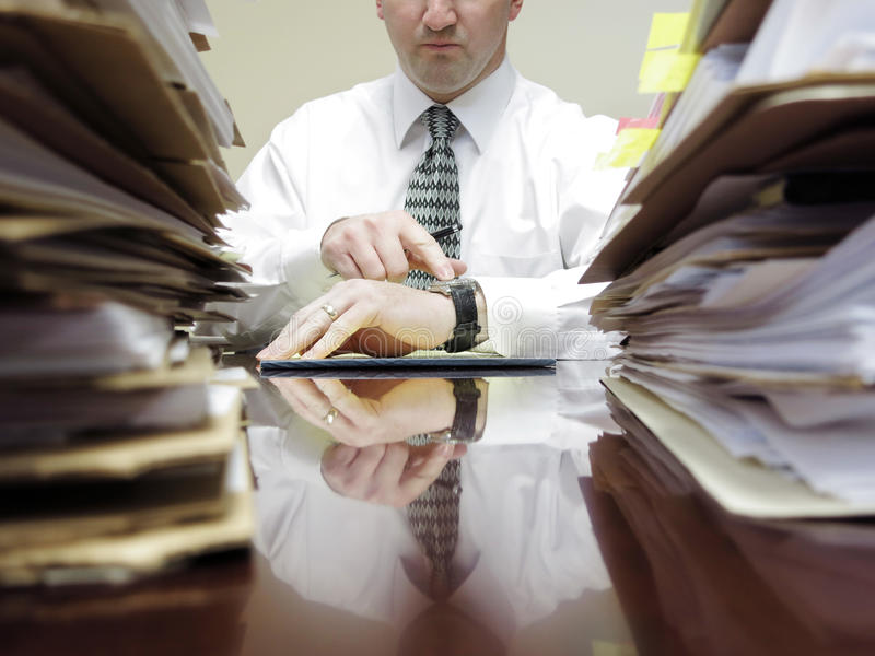 Businessman at Desk with Files Pointing at Watch stock photography