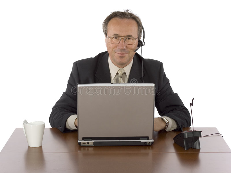 Businessman at the desk with headset stock photography