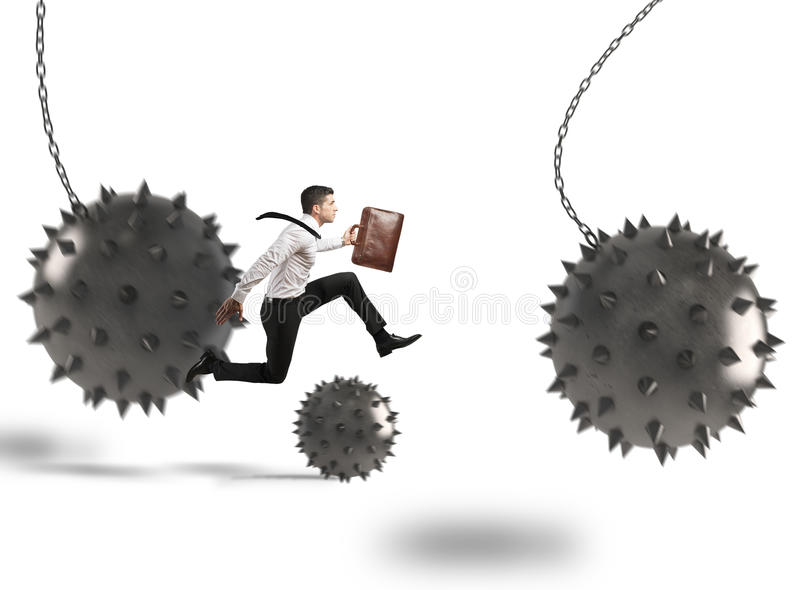 Businessman determined but hampered. Businessman between fierce spiky balls that hinder royalty free stock photos