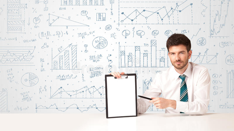 Businessman with diagram background. Businessman sitting at white table with hand drawn diagram background royalty free stock photo