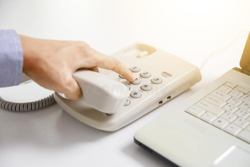 Businessman dial digital telephone with office background. Communication stock image