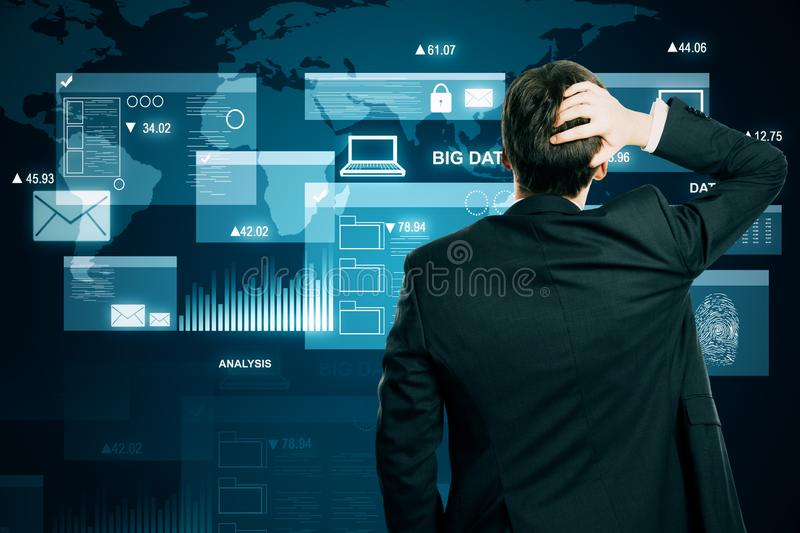 Businessman with digital business interface. Back view of stressed young businessman using digital business interface hologram. Big data and innovation concept stock photos