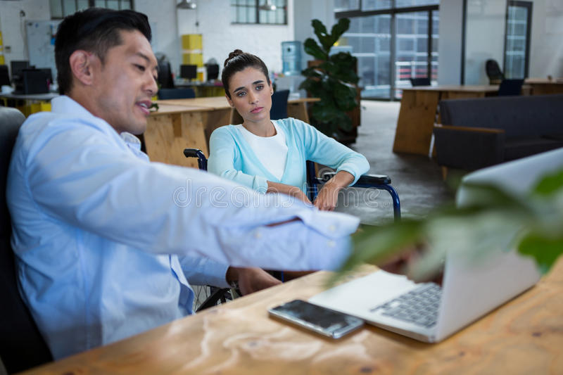 Businessman and disabled woman discussing over laptop stock images