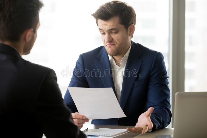 Businessman disappointed with partners offer. Unsatisfied with contract terms businessman disagrees to accept conditions of questionable agreement meeting with royalty free stock photo