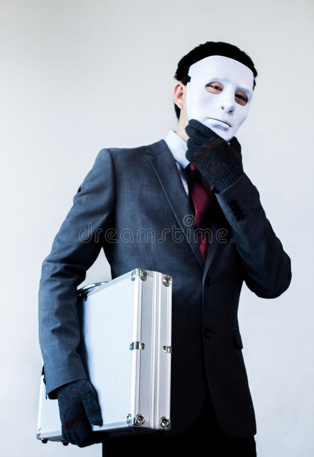Businessman in disguise mask stealing a confidential suitcase.  royalty free stock images