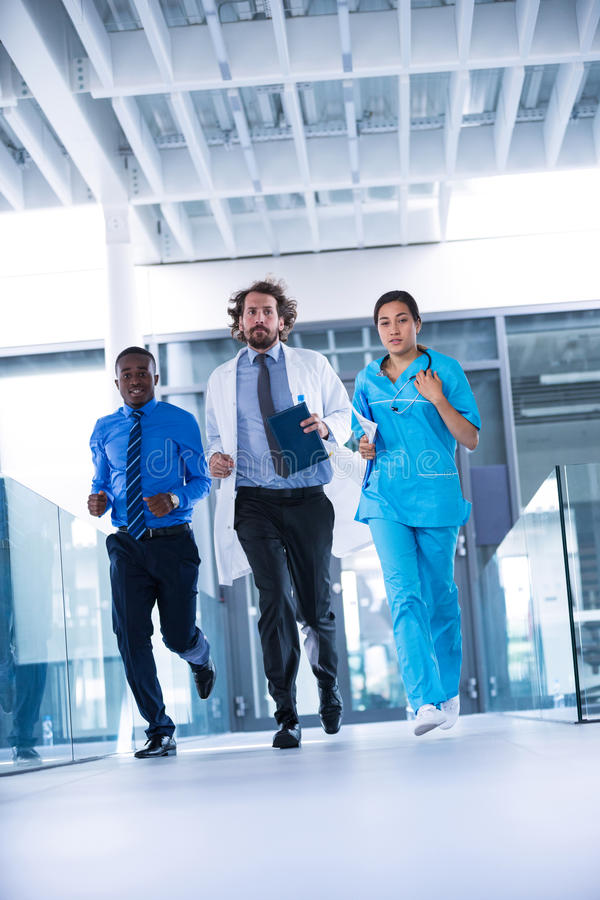 Businessman, doctor and nurse in hospital corridor. During emergency stock images
