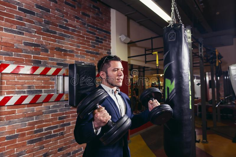 Businessman doing dumbbell biceps wearing formal suit. royalty free stock images