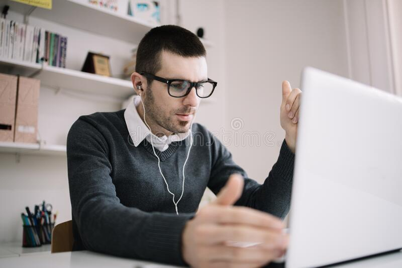 Businessman doing online meeting and video conference. Male employee takes part in online meeting while sitting in office and wearing headphones royalty free stock photography