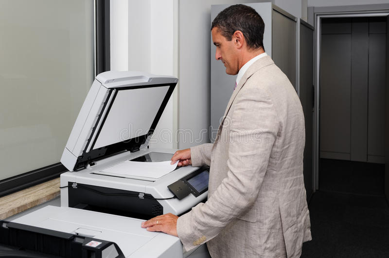 Businessman doing a photocopy. Portrait of a businessman who makes a photocopy as a concept of office life stock images