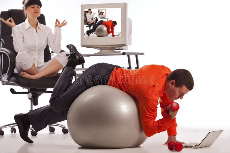 Businessman doing push-ups. Young businessman doing push-ups with dumbbells, looking on laptop screen. His colleague, doing yoga on the office chair royalty free stock photos