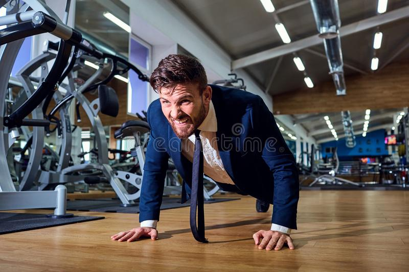 Businessman doing push-ups in the gym. Businessman doing push-ups from the floor in the gym royalty free stock photography