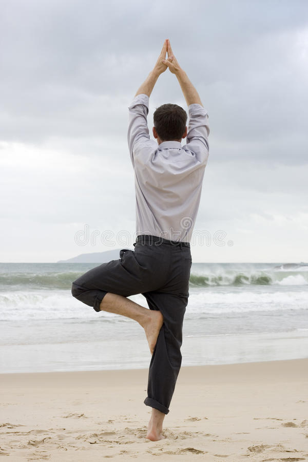 Businessman doing relaxation exercises. On a beach royalty free stock images