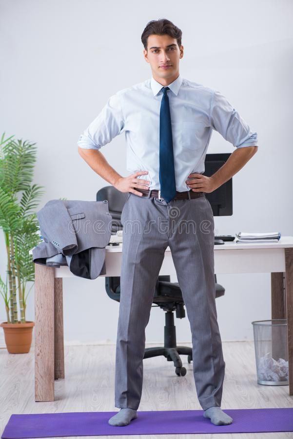 The businessman doing sports in office during break. Businessman doing sports in office during break stock photography