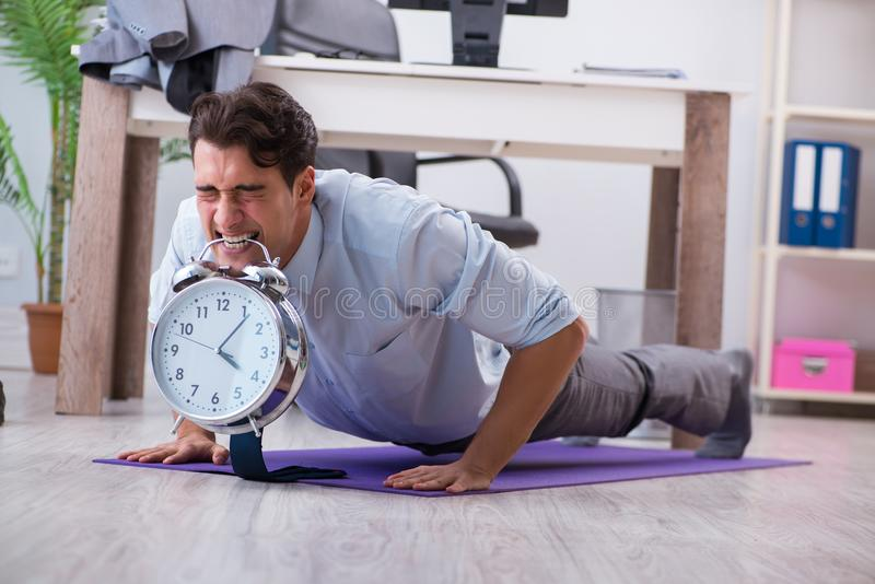The businessman doing sports in office during break. Businessman doing sports in office during break stock photos