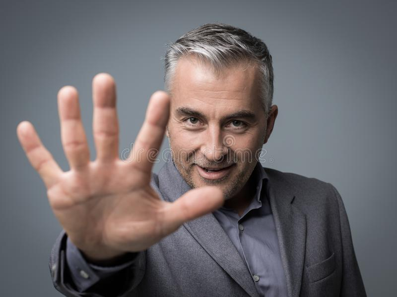 Stop gesture. Businessman doing a stop gesture with his hand and smiling at camera royalty free stock photos