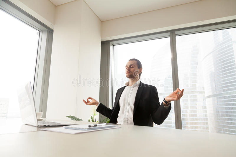 Businessman doing yoga exercises at workplace royalty free stock photo